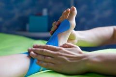 Doctor taping woman injury leg. Stock Photography