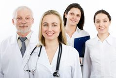 A doctor and team. A female doctor stays in front of her team Stock Images