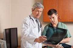 Doctor And Technician Reviewing X-ray Stock Photography