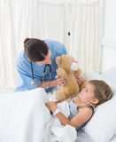 Doctor with teddy bear entertaining sick girl Royalty Free Stock Image