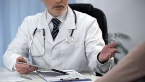 Doctor telling diagnosis to patient, discussing benefits of surgical treatment. Stock photo stock image