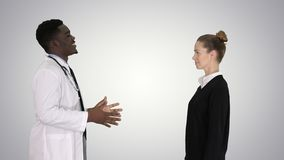 Doctor telling good news and patient leaves on gradient background. stock photo