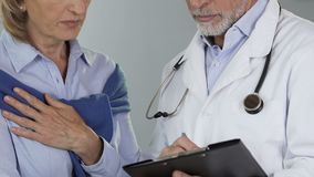 Doctor telling his female patient unfavorable news, breast cancer awareness