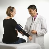 Doctor testing blood pressure. Stock Images