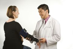 Doctor testing blood pressure. Royalty Free Stock Photo