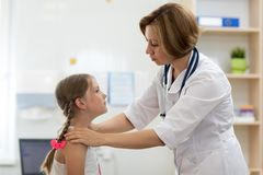 Doctor testing little girl tonsils. Doctor pediatrician testing little child girl tonsils stock image