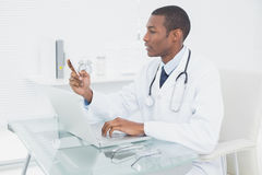 Doctor text messaging while using laptop at medical office Royalty Free Stock Photography