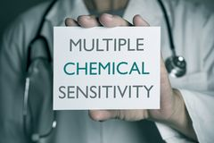 Doctor and text multiple chemical sensitivity. Closeup of a young caucasian doctor man in a white coat showing a signboard with the text multiple chemical Royalty Free Stock Photo