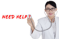 Doctor with text need help. Photo of a female doctor holding a stethoscope with text need help on the futuristic screen Royalty Free Stock Image