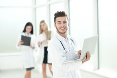 Doctor therapist uses a laptop while standing in the hallway of the clinic. Photo with copy space royalty free stock images