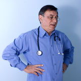 Doctor thinking. Portrait of a middle aged medical doctor with stethoscope around his neck and hands on hips, thinking Stock Photo