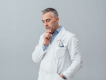 Doctor thinking with hand on chin Royalty Free Stock Photography