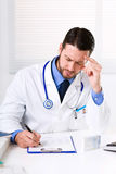 Doctor thinking on prescription stock image