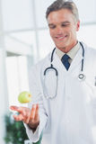 Doctor throwing an apple Royalty Free Stock Photo