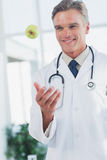 Doctor throwing a green apple Royalty Free Stock Image
