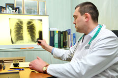Doctor throwing a look to a chest x-ray image. Young male doctor throwing a look to a chest x-ray image royalty free stock image