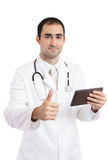 Doctor thumb up. Happy doctor holding digital tablet and showing thumbs up Stock Photos