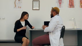Doctor tired of arguing with patient offering her water and a pill to calm down stock video footage
