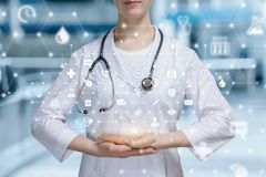 A doctor with a total medical system structure scheme above her hands stock photos