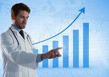Doctor touching air in front of bar charts. Digital composite of Doctor touching air in front of bar charts Stock Photos