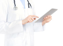 Doctor Touching On Apple iPad2. Doctor in white coat with stethoscope holding and touching on digital tablet pc. Isolated on white Stock Image