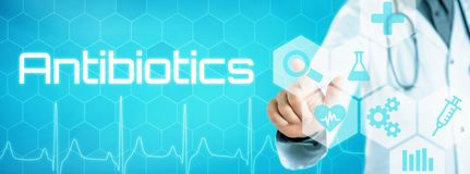 Doctor touching an icon on a futuristic interface - Antibiotics royalty free stock photography
