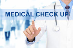 Doctor touching MEDICAL CHECK UP sign on virtual screen. Doctor hand touching MEDICAL CHECK UP sign on virtual screen Stock Photo