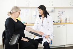 Doctor Touching Senior Patient's Arm Before Blood Test In Clinic. Mid adult doctor touching senior patient's arm before blood test in clinic stock photo