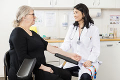 Doctor Touching Senior Patient's Arm Before Blood Test Stock Photo