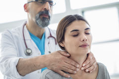 Doctor touching throat of patient stock image