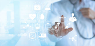 Doctor touching white icon medical on virtual screen, medical te. Doctor in white gown touching white icon medical on virtual screen, medical technology network Stock Photo