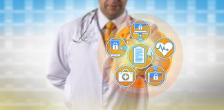 Doctor Transfers Data Between Networked Devices. Unrecognizable doctor synchronizing patient medical records across portable devices. Healthcare concept for Royalty Free Stock Photography
