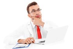 Doctor trastornado con el ordenador portátil y los documentos Foto de archivo