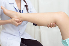 Doctor the traumatologist examines patient's knee Stock Image