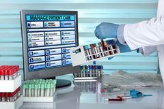 Doctor with tray blood samples in hands in front of computer of Royalty Free Stock Image