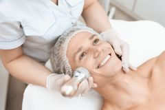 The doctor treats the male skin with a photoepilator. The man is lying on the couch and is smiling. They are in a modern beauty salon Royalty Free Stock Photos