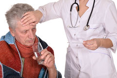 Doctor treats sick elderly man Royalty Free Stock Photography