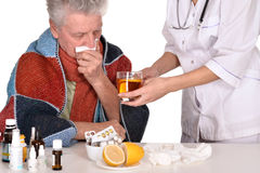 Doctor treats sick old man Royalty Free Stock Image