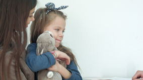 Doctor trying to cheer up little girl patient hugging her bunny toy stock video