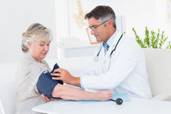 Doctor tying blood pressure belt on female patients hand Stock Photo