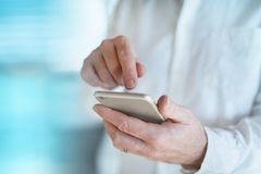 Doctor types information into his mobile phone. Doctor writes information in his mobile phone in front of a bright blue background royalty free stock photos