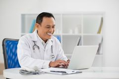 Doctor typing. Portrait of mature doctor sitting in his office and typing on laptop Royalty Free Stock Photos