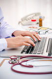 Doctor typing on computer Stock Images