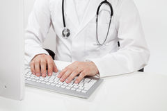 Doctor typing on computer Stock Photo