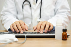 Doctor is typing diagnose on computer keyboard Royalty Free Stock Photography