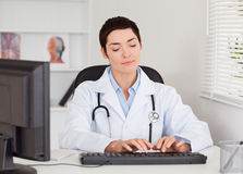 Doctor typing with her computer Royalty Free Stock Image