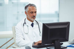 Doctor typing on his computer. In cabin Stock Photos