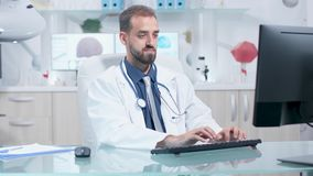 Doctor typing on his computer then he writes in clipboard