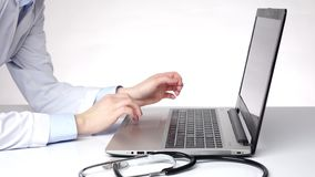 Doctor typing important information on the computer, white stock footage