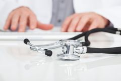 Doctor typing on keyboard. Close-up Of Doctor's Hand Typing On Keyboard In Front Of Stethoscope Stock Images